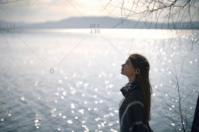 Pensive Caucasian girl at lake looking up