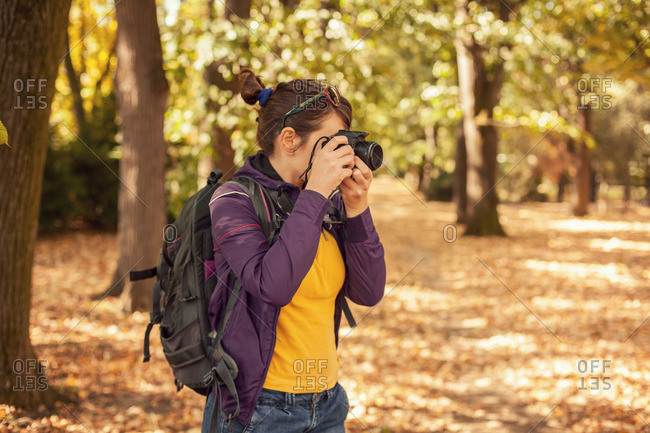 Woman taking pictures in autumn woods