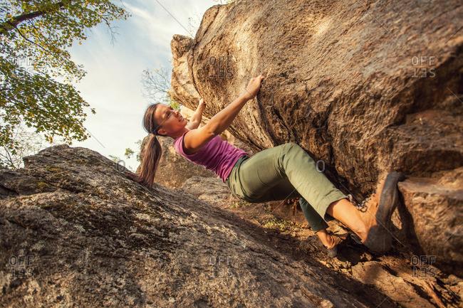 Woman climbing by rock crevice