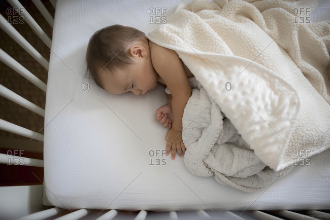 Portrait of a baby sleeping in crib with blanket