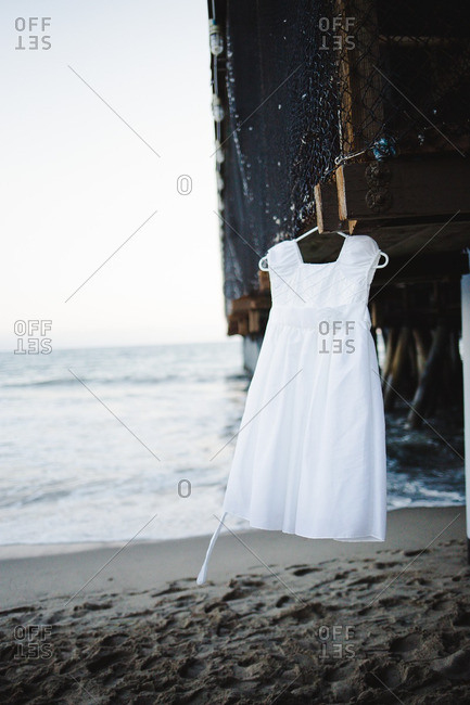 White dress hanging from beneath a pier near the ocean