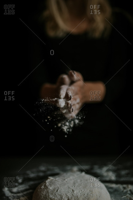 Woman preparing to dust a ball of dough with flour