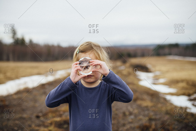 Little girl looking through a round glass object