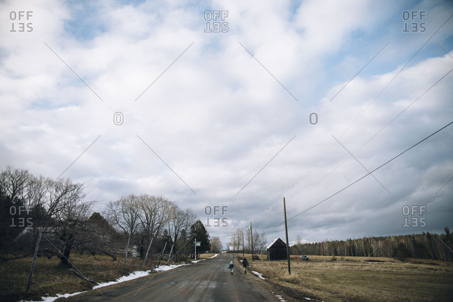 Two children running on a country road with melting snow