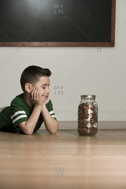 Boy looking at jar of money