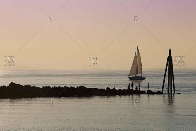 Children playing on large rocks by ocean with sailboat