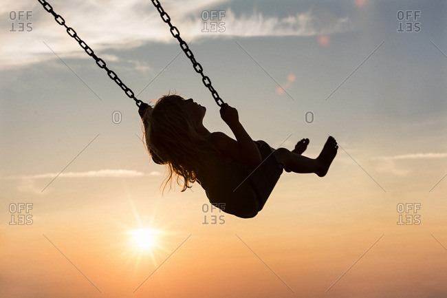 Little girl swinging on a swing at sunset