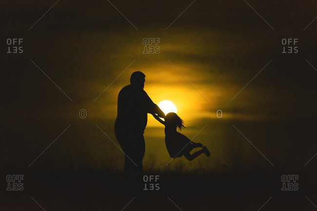 Silhouette of father swinging daughter around sunset