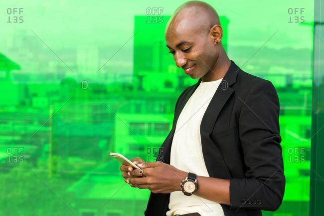 Smiling gay Black man texting near green window