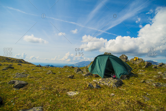Green tent on rocky mountain