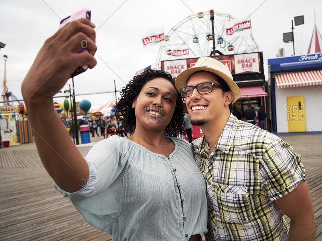 Couple posing for selfie on boardwalk at amusement park