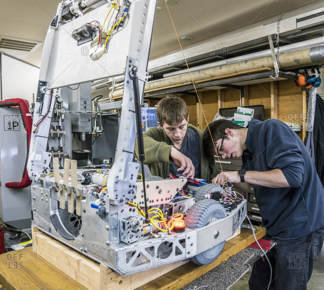 Caucasian robotics students adjusting machinery