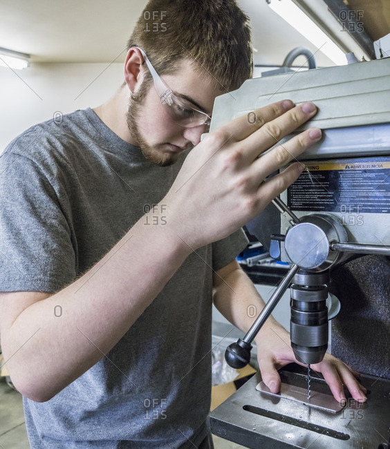 Student using drill press in workshop