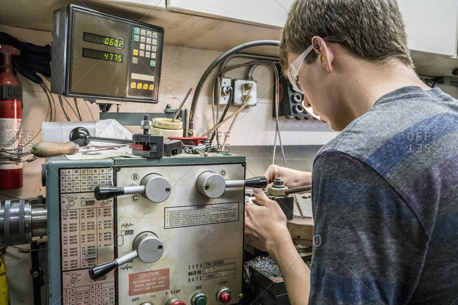 Caucasian students adjusting machinery in workshop