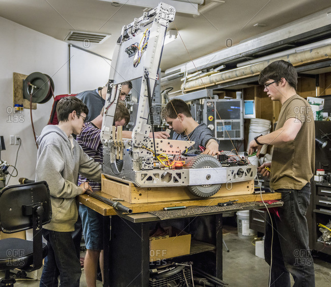 Caucasian robotics students and teacher adjusting machinery