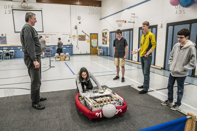 Robotics students and teacher examining robot