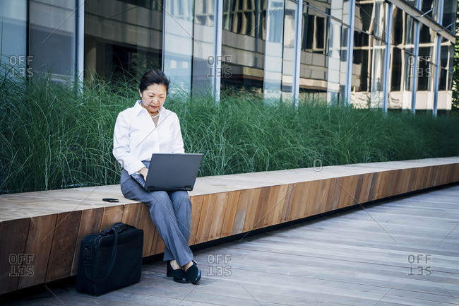 Businesswoman sitting on bench using laptop