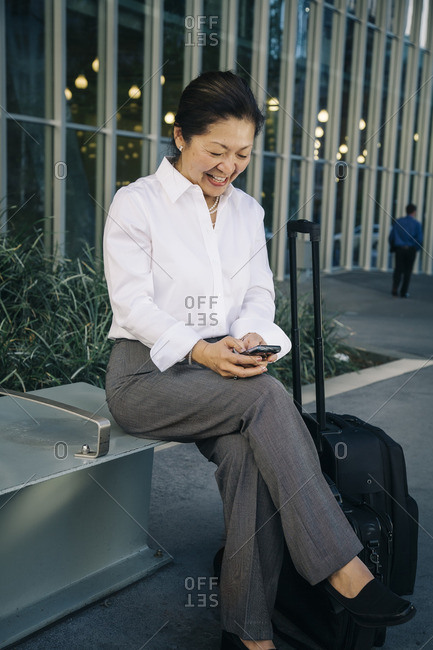 Businesswoman sitting on bench with suitcase texting on cell phone