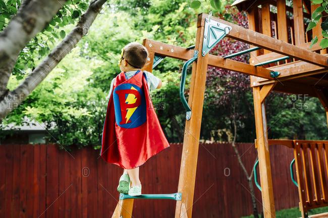 Caucasian boy wearing superhero costume climbing on backyard playground