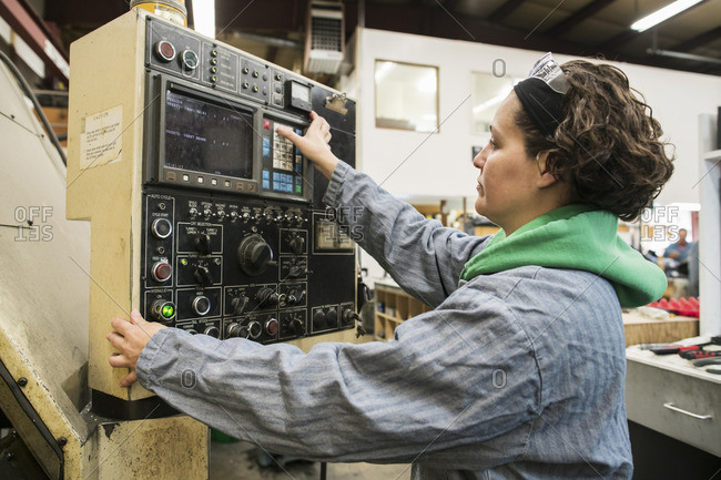 Hispanic worker using control panel in factory