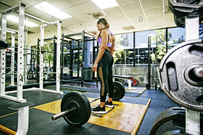 Mixed Race woman standing over barbell in gymnasium