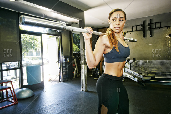 Mixed Race woman stretching with barbell in gymnasium