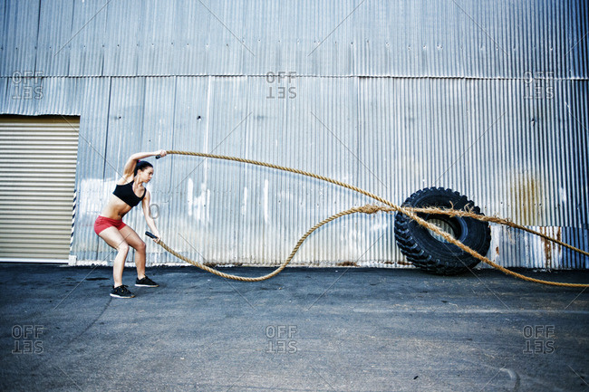 Mixed Race woman working out with heavy ropes outdoors