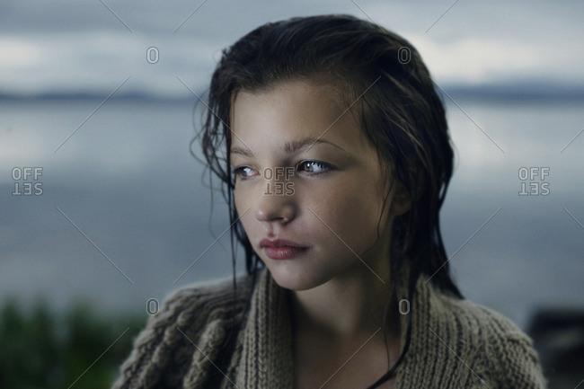 Pensive Caucasian girl with wet hair at lake