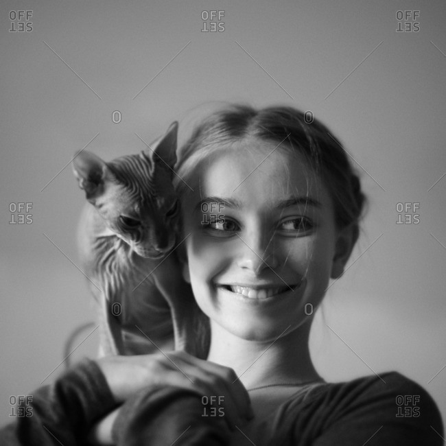 Smiling Caucasian girl with hairless cat on shoulder
