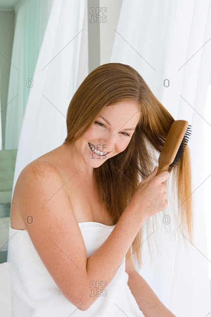 Young woman brushing hair