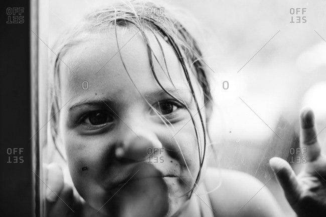 Portrait of young girl with face pressed against glass