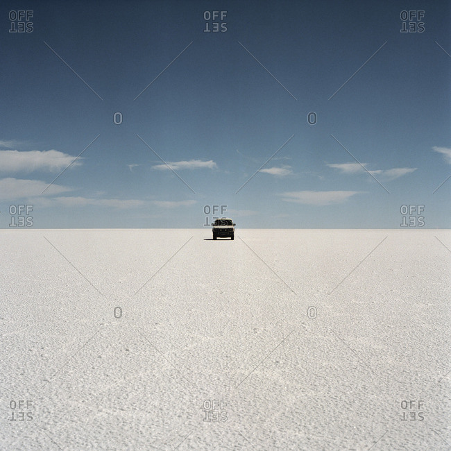 Vehicle parked on barren salt flat, Bolivia