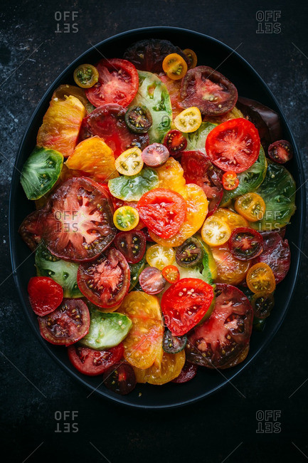 Colorful heirloom tomatoes sliced in an oval dish