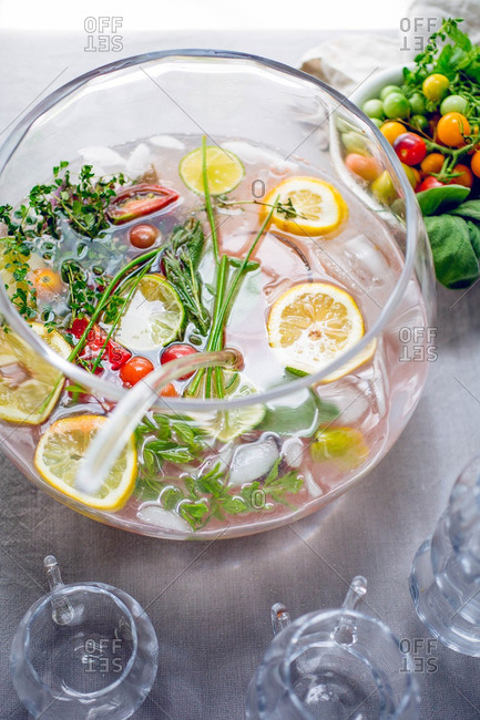 Overhead view of bowl of punch with citrus and herbs