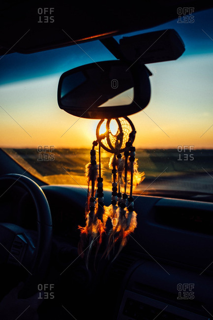 Dream catcher hanging from rearview mirror of vehicle at sunset