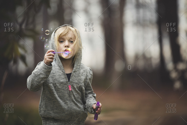 Girl blowing bubbles in woods