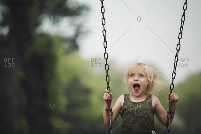 Girl yelling on swing set