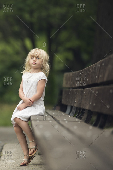 Girl sitting up on rural bench