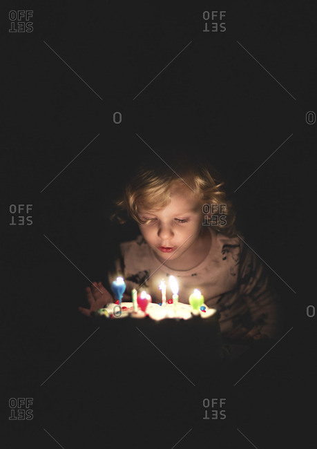 Girl in darkness blowing out candle