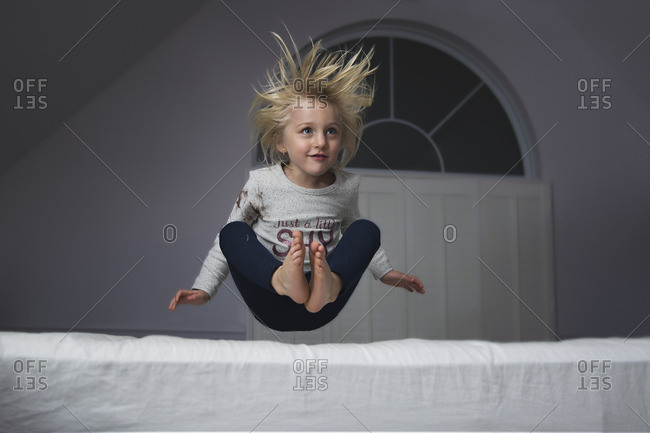 Girl bouncing onto a bed