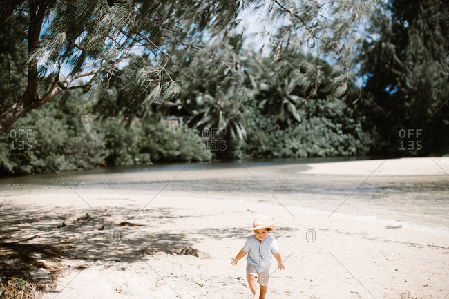 Boy in hat walking sandy river shore