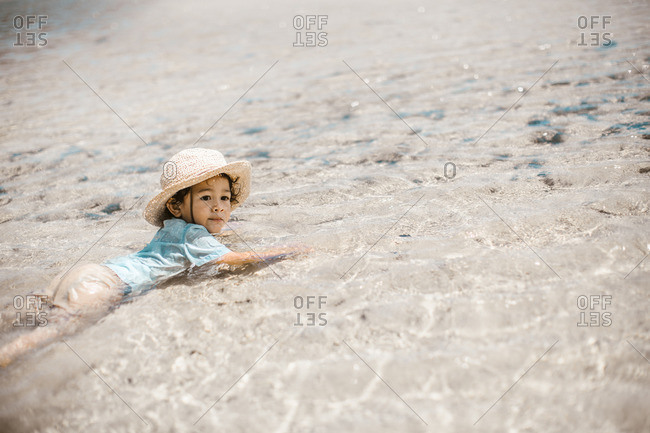 Boy in hat lying in water