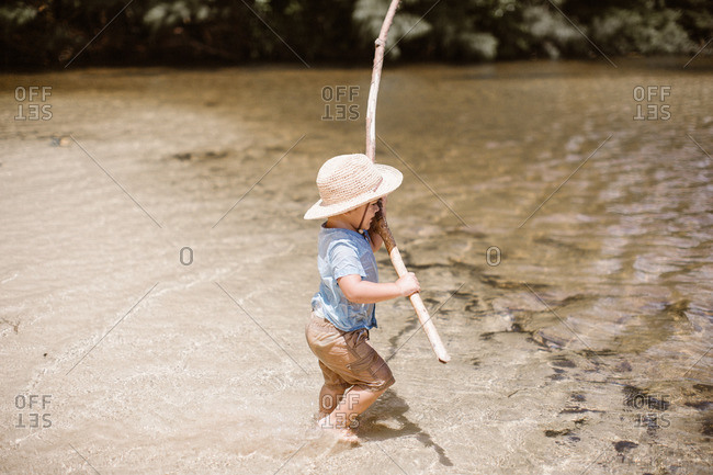 Boy in hat in river with stick