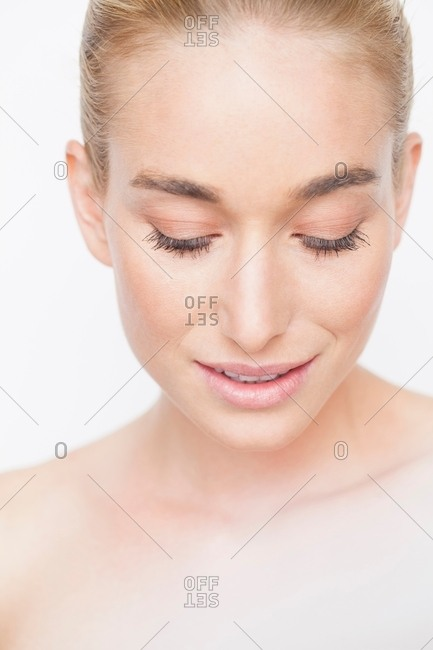 Close up portrait of woman with bare shoulders and hair slicked back looking down smiling
