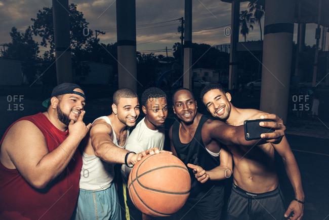 Men holding basketball using smartphone to take selfie