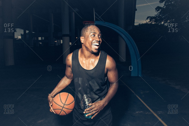 Man on basketball court holding basketball looking away smiling
