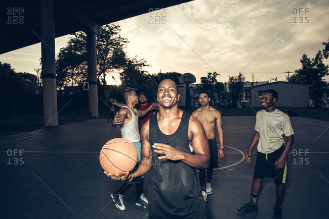 Man with friends on basketball court holding basketball smiling