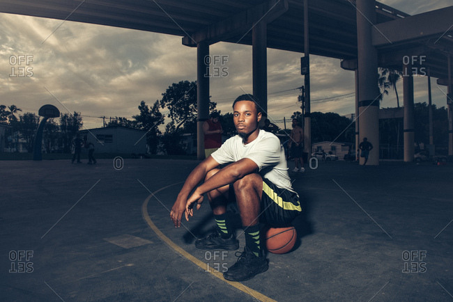 Man on basketball court sitting on basketball looking at camera