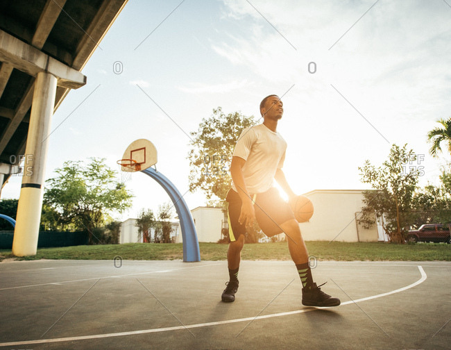 Men on basketball court holding basketball looking away