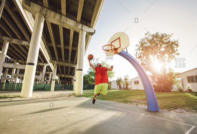 Low angle view of man on basketball court in mid air jumping for basketball hoop